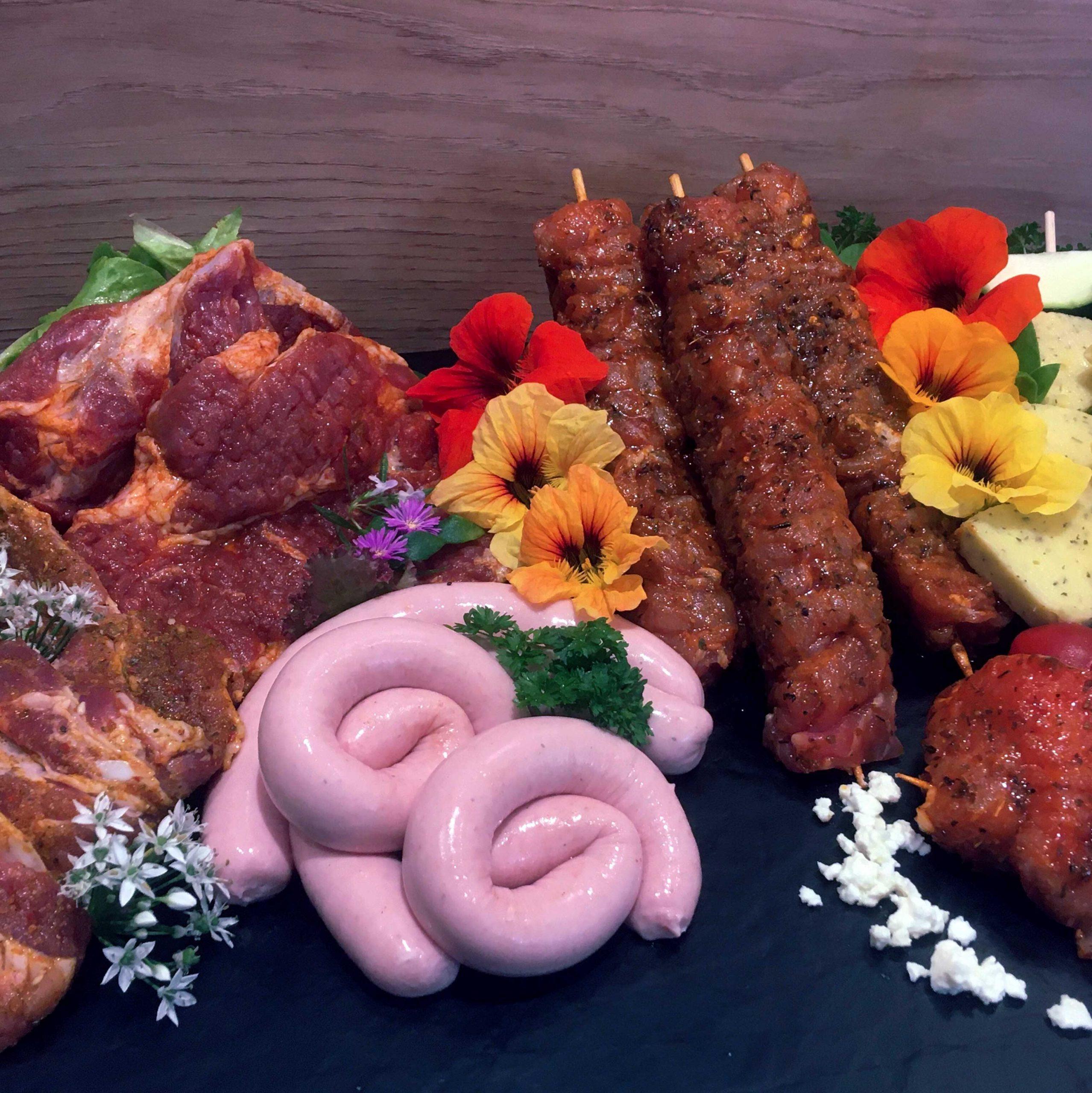 Eine Platte mit Grillspezialitäten, Bratwurst, Steak und co.